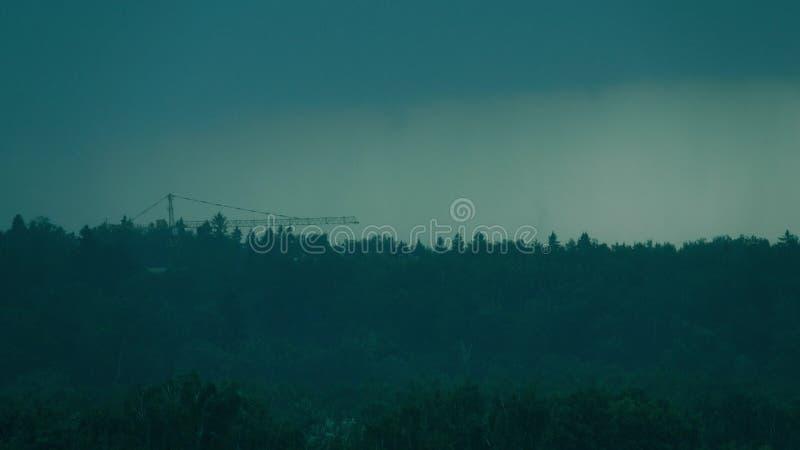 E Grúa de construcción y árboles forestales distantes imagen de archivo libre de regalías
