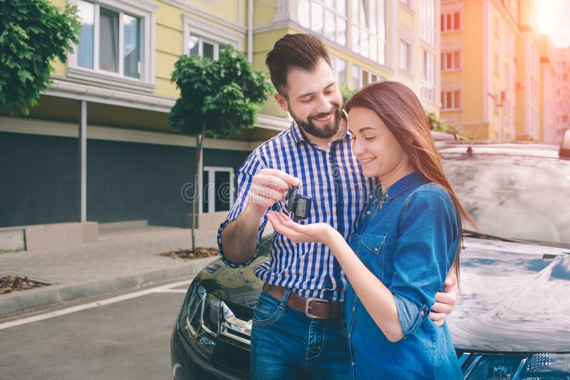 E have made the right choice. Handsome young men standing near the car at the dealership hugging his girlfriend and royalty free stock photos