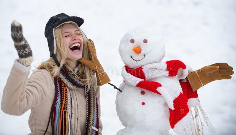 E Het gelukkige meisje plaing met een sneeuwman op een sneeuw de wintergang Het maken van sneeuwman en de winterpret gek royalty-vrije stock fotografie