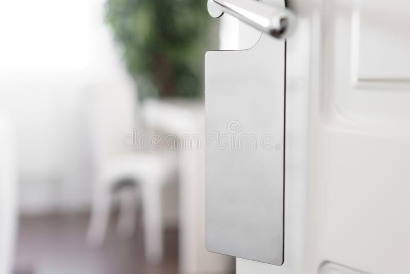 E Het lege witte vliegermodel hangt op deurhandvat Pamfletontwerp stock foto's
