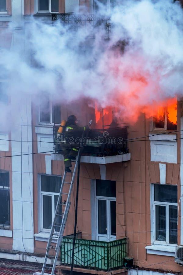 E Het sterke heldere licht en de clubs, rook betrekken venster van hun brandend huis brandbestrijders stock afbeelding
