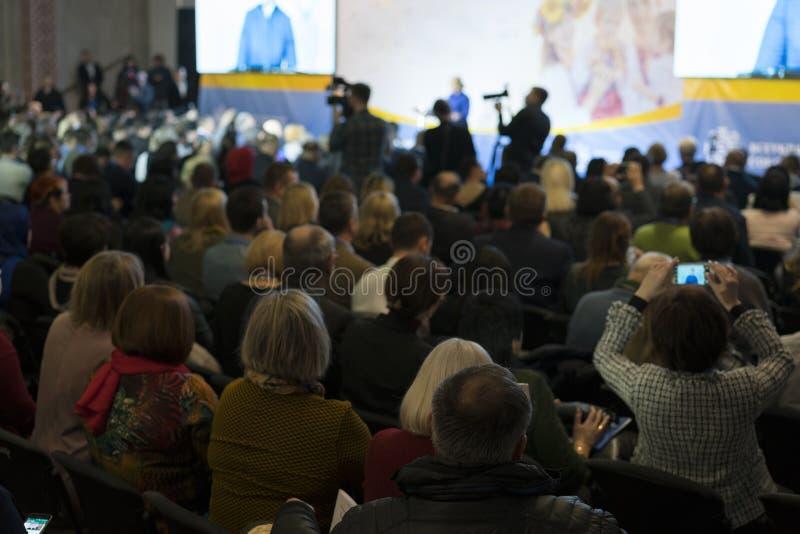 E Hombre de negocios y gente que escuchan en la conferencia foto de archivo