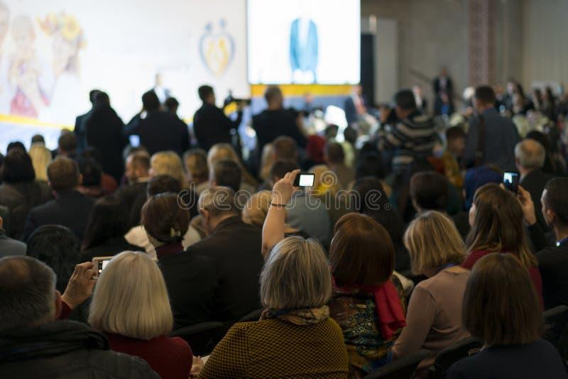 E Hombre de negocios y gente que escuchan en la conferencia imagenes de archivo