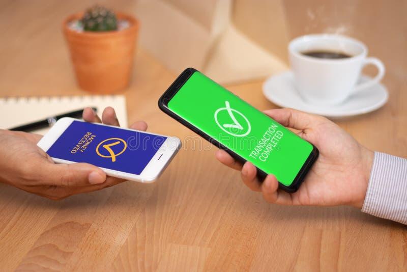 E hombres de negocios que usan la cartera del uso en el smartphone móvil para el dinero de la transferencia a otro fotos de archivo