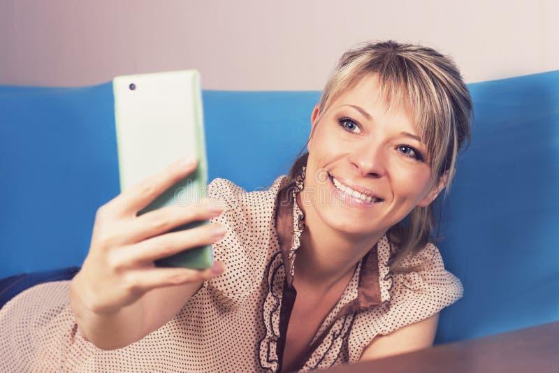E Hon ser hennes smartphone och gör en selfie arkivfoto