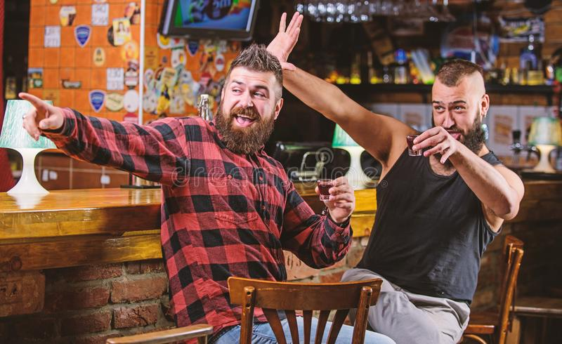 E i 与朋友的行家残酷有胡子的人饮用的酒精酒吧柜台的 人被喝 免版税库存图片