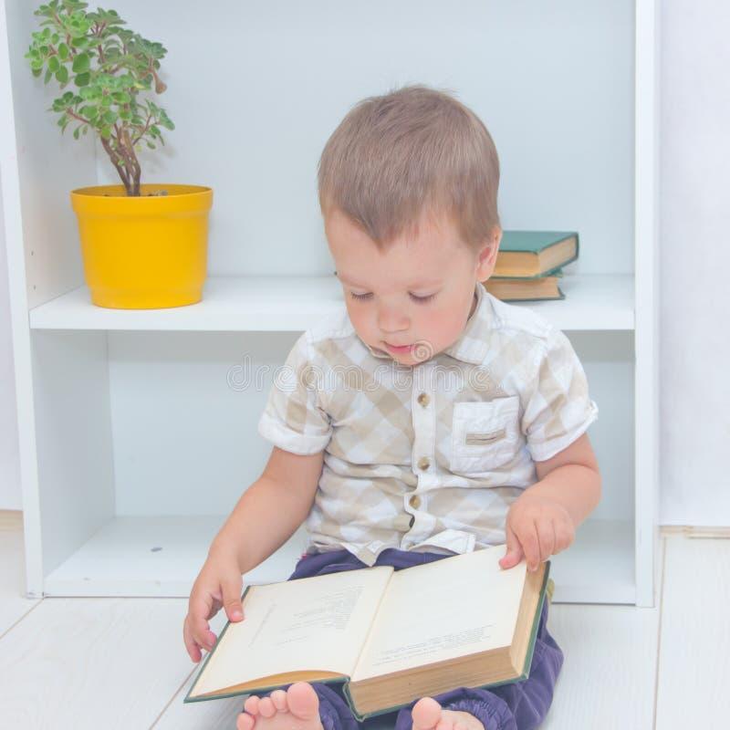Un ragazzino è seduto sul pavimento e io fotografia stock