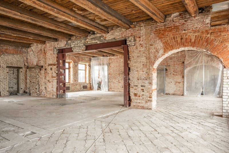 E Int?rieur de studio de grenier dans la vieille maison Grandes fen?tres, mur de rouge de brique Maison photographie stock libre de droits