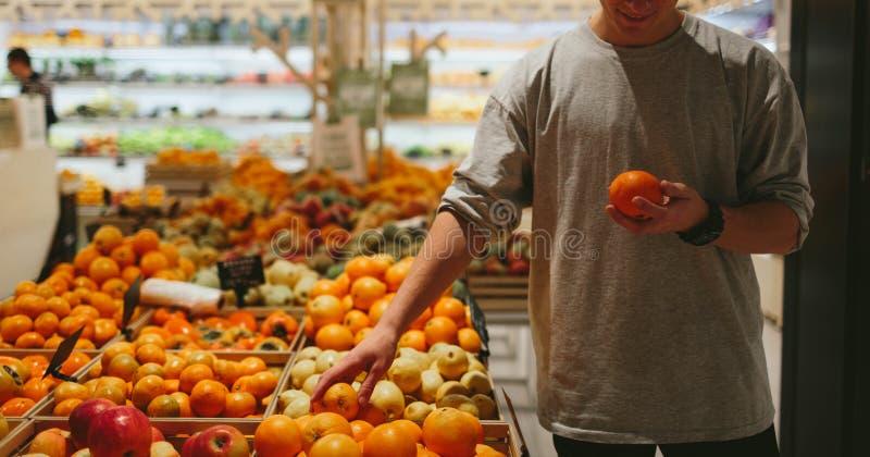 E Jeunes hommes beaux poivre et panier oranges tout en se tenant dans un magasin de nourriture photographie stock libre de droits