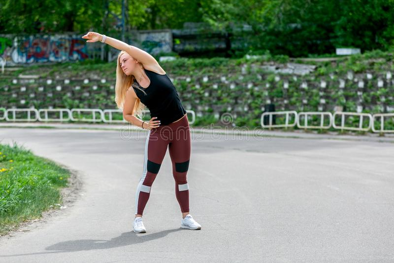 E Jonge vrouw die alvorens op te leiden het doen uitoefent om haar spieren en verbindingen uit te rekken opwarmen Sportief jong b royalty-vrije stock afbeeldingen