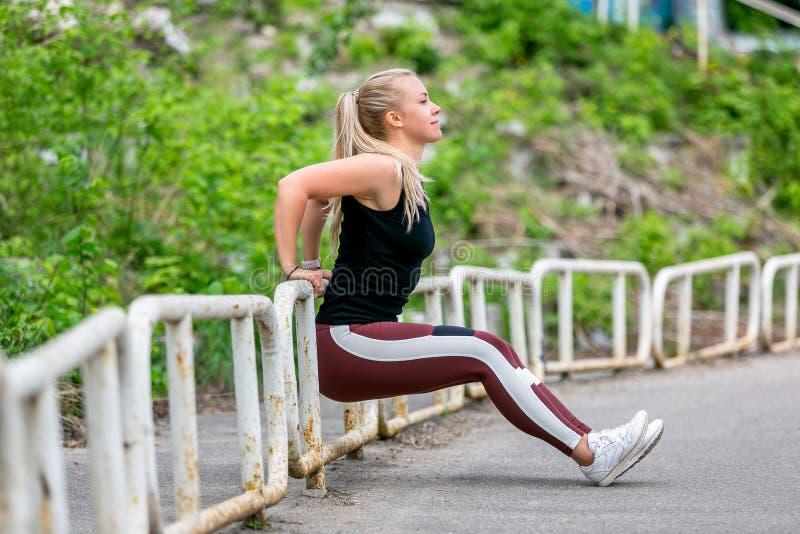 E Jonge vrouw die duw UPS van de pijler doen Sportief jong blondemeisje op een zonnige dag bij het stadion Gezond stock foto's