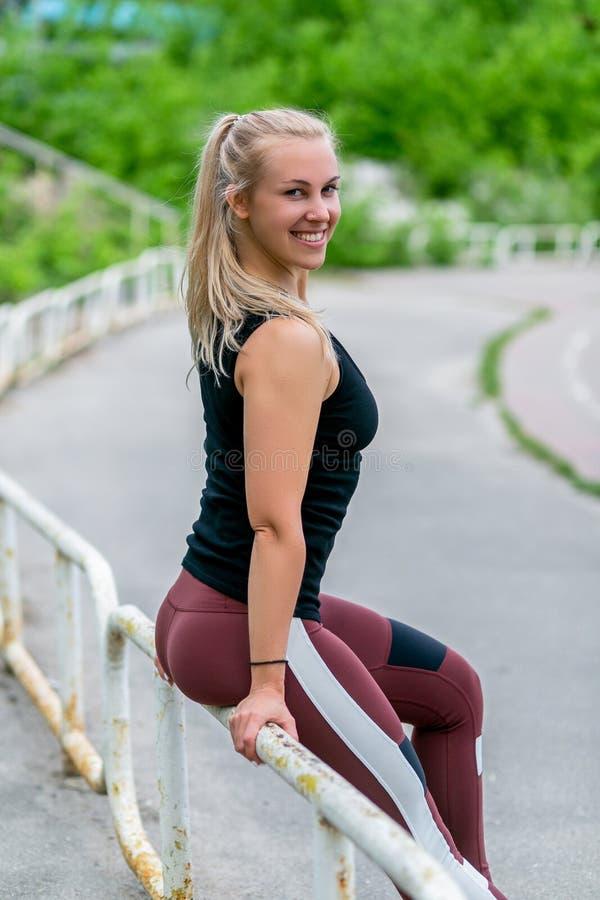 E Jonge vrouw die na oefening rust Training bij het stadion Gezond het levensconcept stock afbeelding