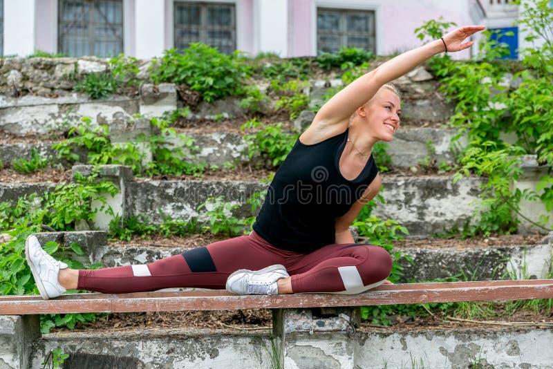 E Jonge vrouw die op de bank opwarmen alvorens op te leiden het doen uitoefent om haar spieren en verbindingen uit te rekken spor royalty-vrije stock afbeeldingen