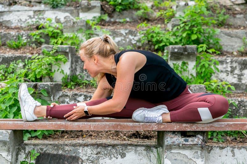 E Jonge vrouw die op de bank opwarmen alvorens op te leiden het doen uitoefent om haar spieren en verbindingen uit te rekken spor royalty-vrije stock fotografie