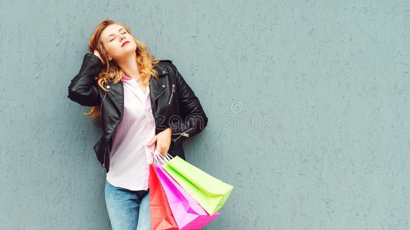 E Junge sch?ne Einkaufenfrau w?hrend des Verkaufs, der viele bunten Einkaufenbeutel getrennt auf wei?em Hintergrund im Studio anh stockbilder