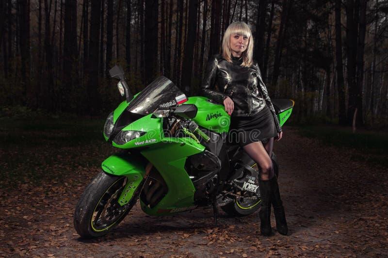 E 10 2016 - junges schönes Mädchen auf einem Portmotorrad Kawasaki zx-10r an der dunklen Straße lizenzfreie stockfotos