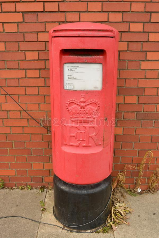 E K , Czerwiec 20, 2019 - tradycyjny brytyjski czerwony postbox blisko ściany z cegieł zdjęcie stock