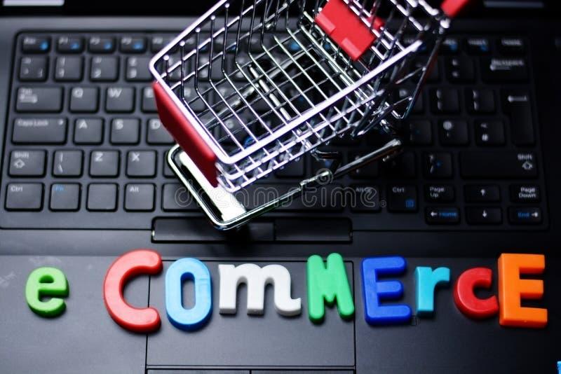 E-kommers text från färgrika bokstäver på bärbar datortangentbordet med den metalliska shoppingspårvagnen royaltyfri fotografi