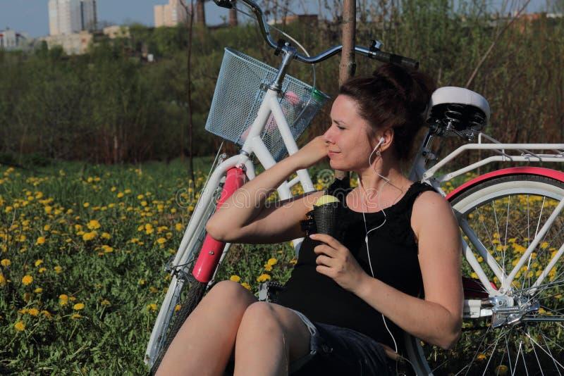 E ?l se sienta al lado de la bici, come el helado y escucha la m?sica Los dientes de le?n est?n floreciendo, fotos de archivo