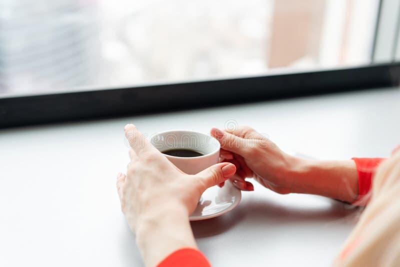 E La femme dans le costume de corail rouge boit du café à une haute table près de la fenêtre jeune images libres de droits