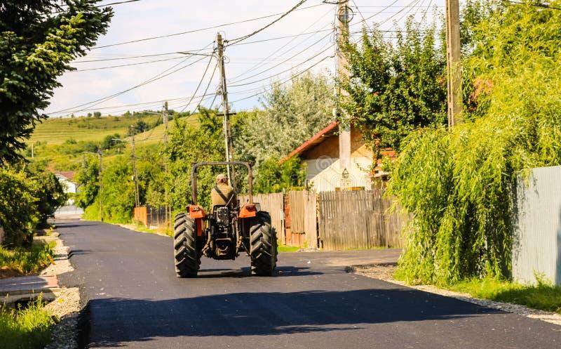 E Landbouwer in rode tractorritten op het nieuwe asfalt in het zonlicht royalty-vrije stock foto's