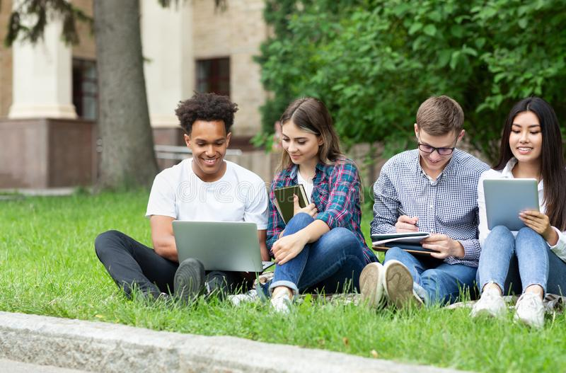 E-learning concept. Diverse students with devices in campus stock photo