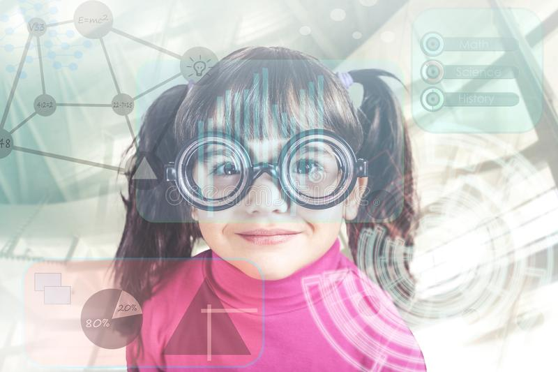 E-learning concept. Little genius girl in front of digital hud interface and icons stock image