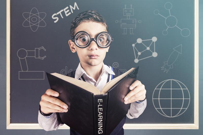 E-learning and futuristic STEM education technology concept. Funny genius boy in front of a blackboard stock photography