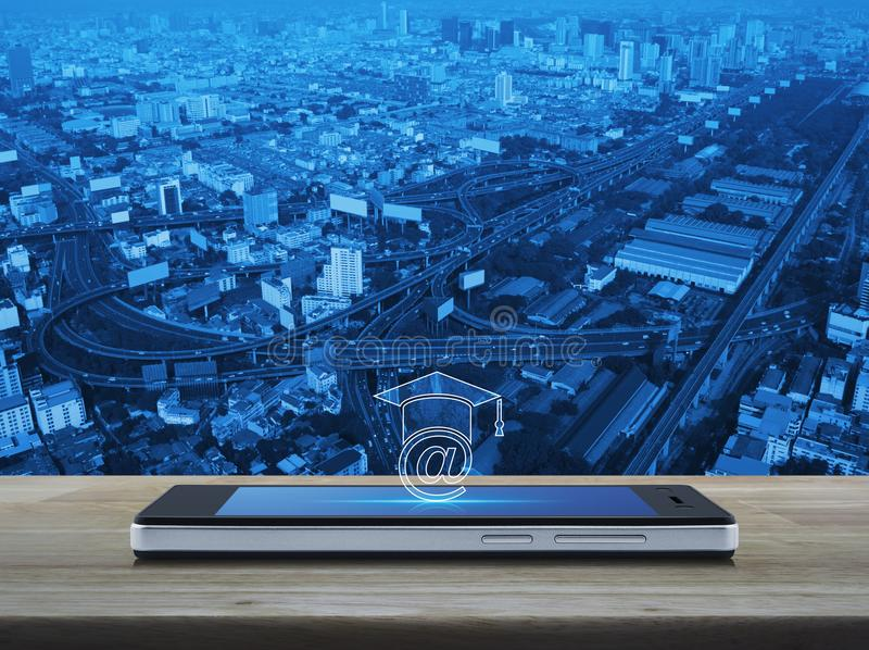 Study online concept. E-learning icon on modern smart phone screen on wooden table over city tower, street and expressway, Study online concept stock photography