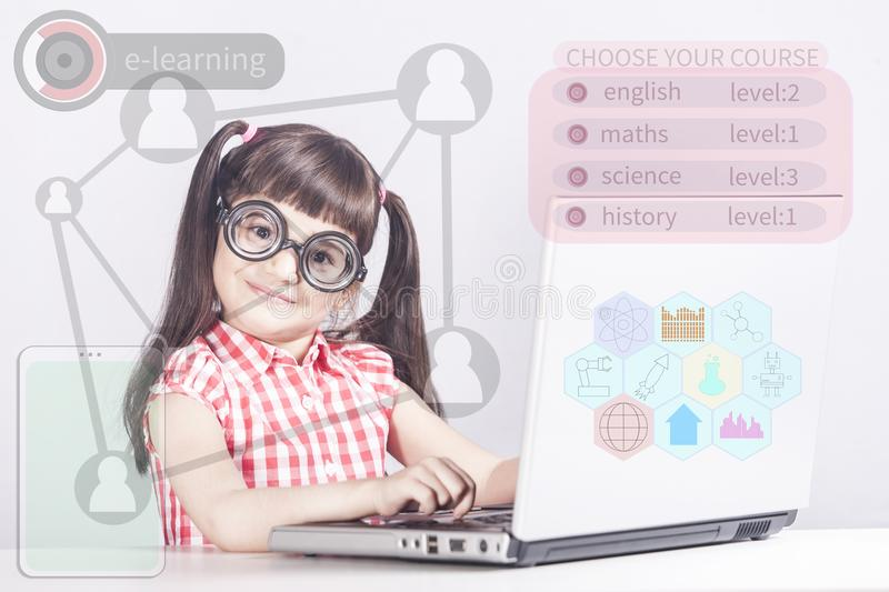 E-learning kids concept. Llittle genius girl in front of a computer with digital hud interface and icons royalty free stock images
