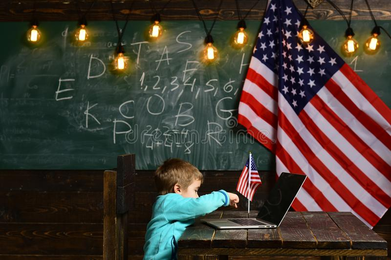 E-learning or online courses at home schooling. Little boy with laptop for business at American flag. Patriotism and stock photo