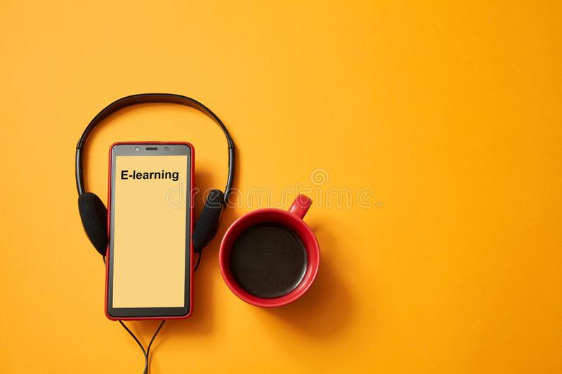 E-learning or online education concept. Webinar, internet lesson or courses. Headphones, coffee cup on yellow background stock images