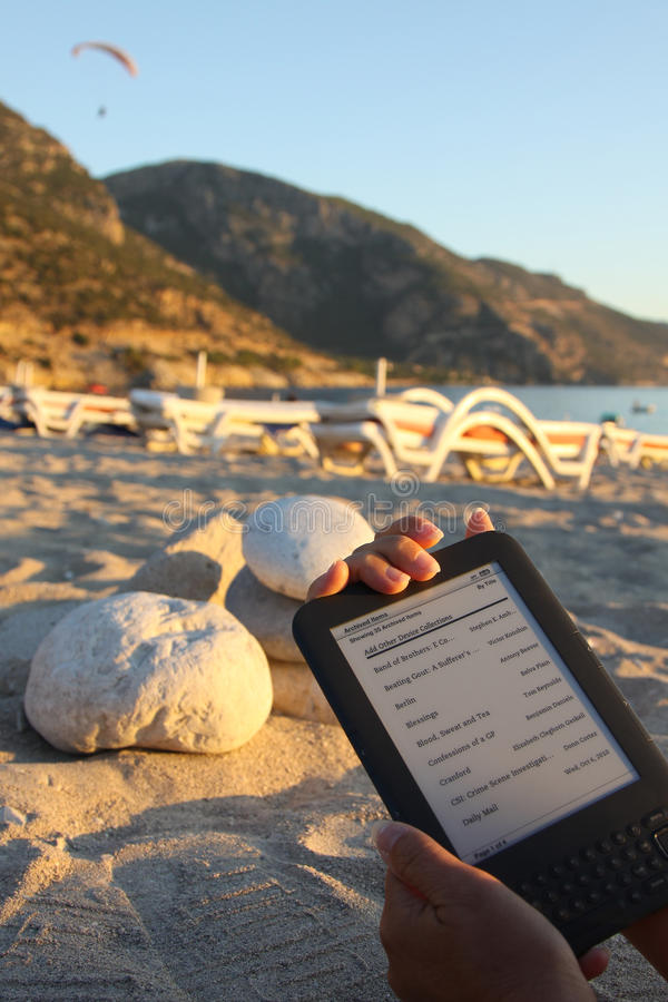 E-Lecteur sur la plage photographie stock libre de droits