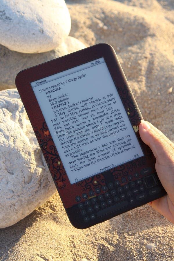 E-lettore che usando sulla spiaggia immagine stock