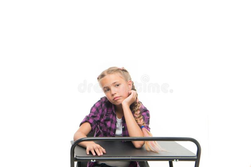 E Li??o aborrecida O aluno furado menina senta-se na mesa Introdu??es do ensino convencional De volta a foto de stock