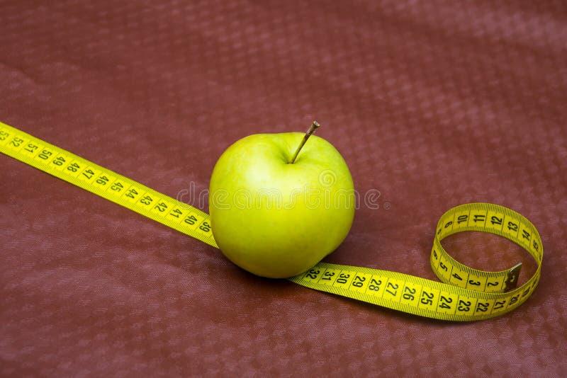 E m?tande band f?r ?pple frukter f?r viktf?rlust r genomskinligt f?r glass fruktsaft f?r bild f?r mat f?r ?pplen f?r ?pple 3d beg arkivfoton