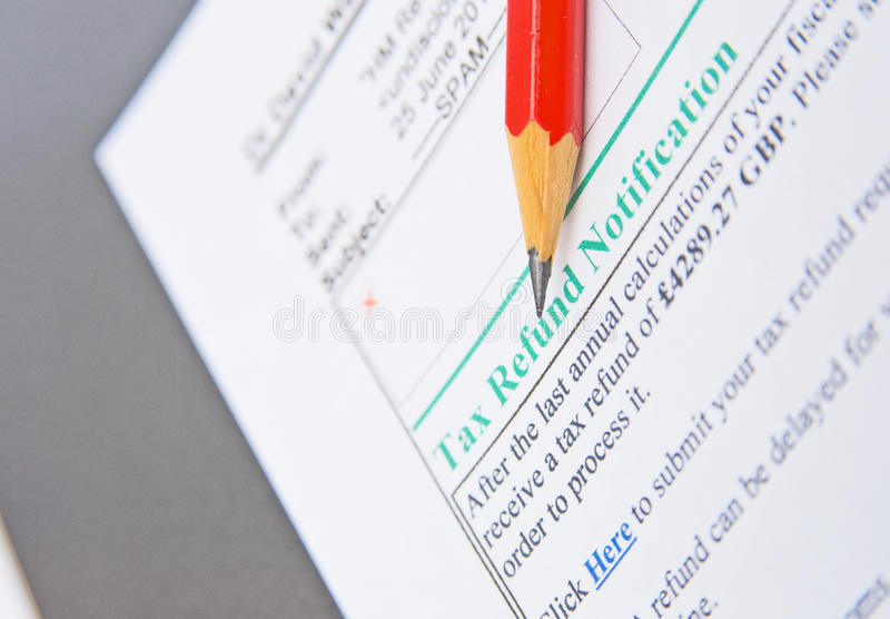E-mail fraud: tax refund method. An image with selective focus of a typical e-mail pretending to be notification of a tax refund. A red pencil points to the stock photo