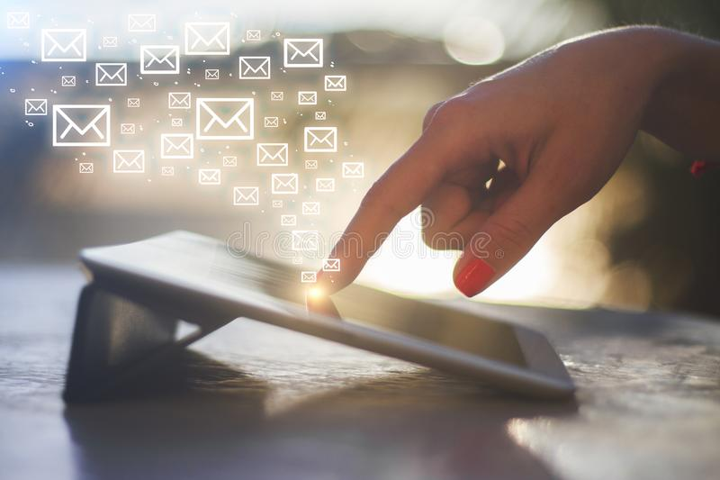 E-mail marketing concept. Side view of female hand using tablet with digital email icon on blurry background with sunlight. E-mail marketing concept royalty free stock photo