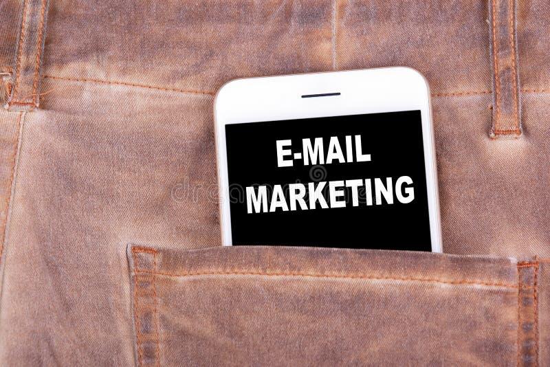 E-mail Marketing Smartphone in jeanszak Technologiezaken en mededeling, reclameachtergrond stock afbeelding