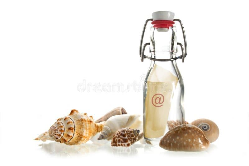 E-mail w butelce między morze skorupami odizolowywać na bielu zdjęcie royalty free
