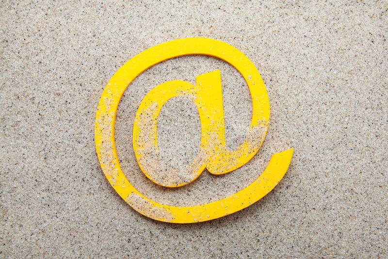 E-mailsymbool in het zand stock afbeelding