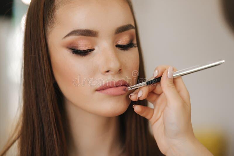 E Main du maître de maquillage, lèvres de peinture de modèle roux de jeune beauté Composez dans le processus image stock