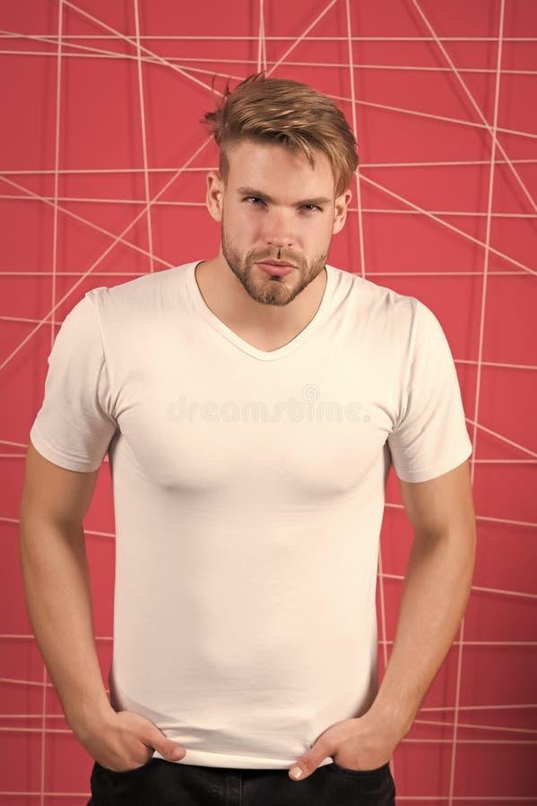 E Manlighetbegrepp Man med borstet på den strikta koncentrerade framsidan, rosa färg arkivbild