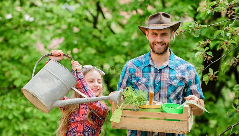 E Menina e paizinho feliz do homem Dia de terra pa?s da vila da mola Ecologia Lata molhando fotos de stock