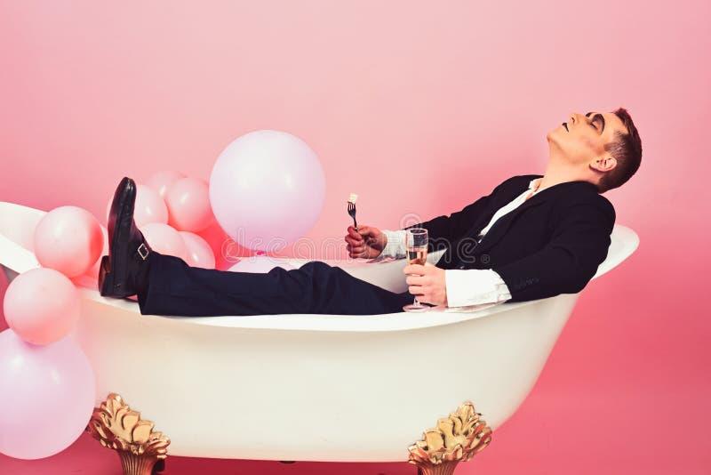 E Mimicar o ator apreciam banhar-se na banheira Mimicar o homem tem o partido da celebração com alimento e bebida fotografia de stock
