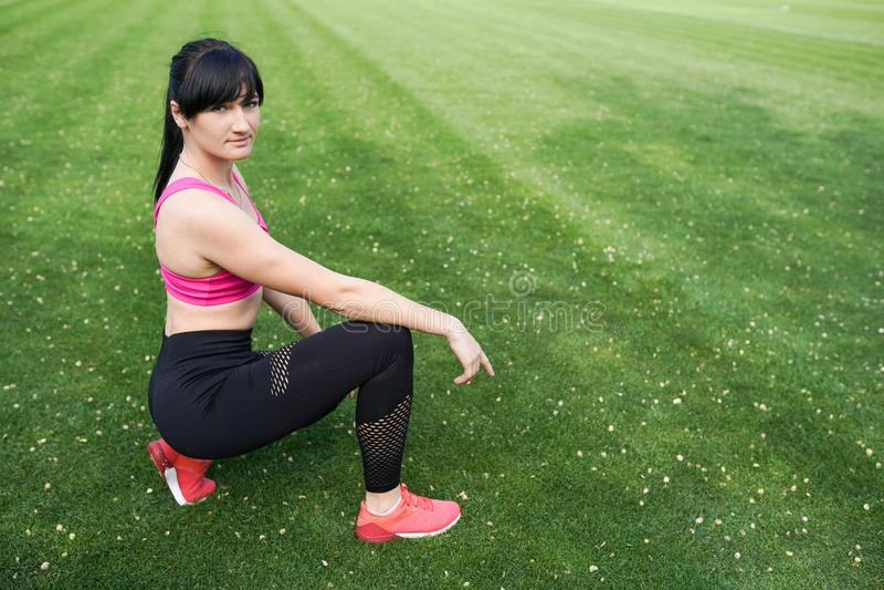 E Modello femminile in abiti sportivi che si esercitano all'aperto immagini stock libere da diritti