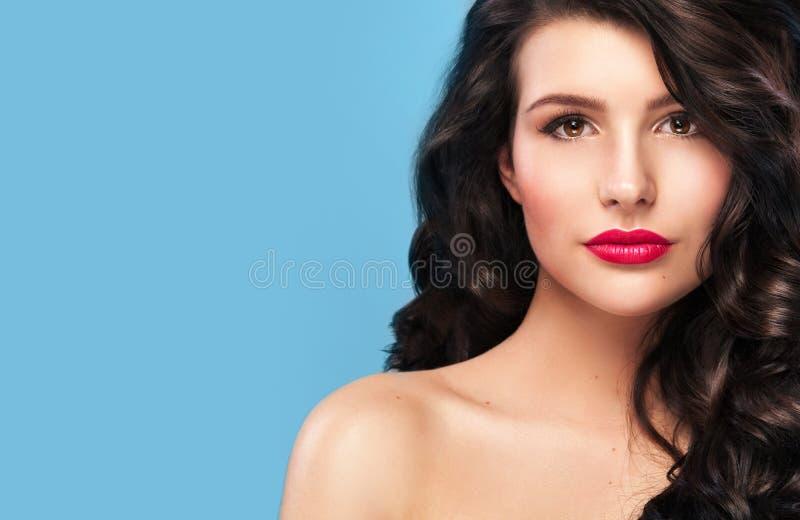 E Modelo bonito, penteado encaracolado no fundo azul fotografia de stock royalty free