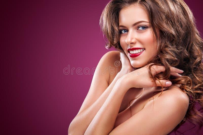 E Modelo bonito, penteado encaracolado no fundo vermelho imagem de stock royalty free