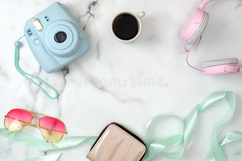 E Modern fotokamera, kopp kaffe, handv?ska, solglas?gon, h?rlurar p? marmor royaltyfri foto
