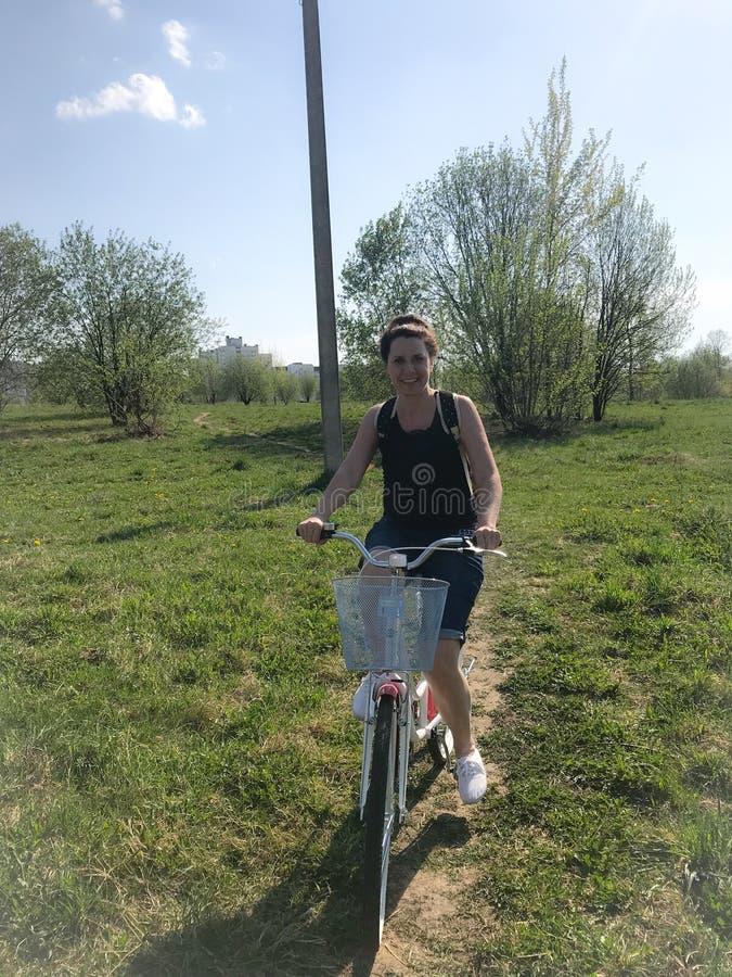 E Montando uma bicicleta, atr?s de uma trouxa do turista Os dentes-de-le?o est?o florescendo, grama nova s?o fotografia de stock royalty free